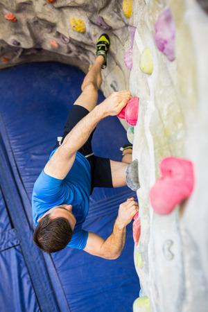 recreational climbing: Fit man rock climbing indoors at the gym