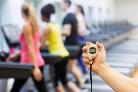 cuerpo hombre: Entrenador que muestra el reloj de parada en el gimnasio Foto de archivo