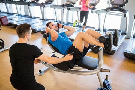 sit ups: Fit man doing sit ups with trainer at the gym