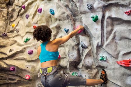 escalando: Mujer roca Fit escalada bajo techo en el gimnasio