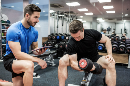 weight training: Fit man working out in weights room at the gym Stock Photo