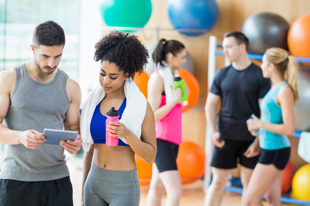 personal trainer woman: Client and trainer looking at tablet pc at the gym Stock Photo
