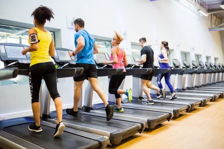 jogging: Fit people jogging on treadmills at the gym Stock Photo