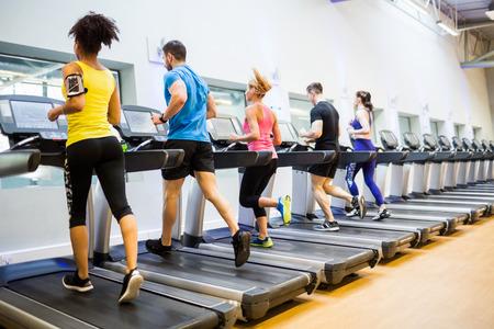 Les gens en forme de jogging sur tapis roulant à la gym Banque d'images