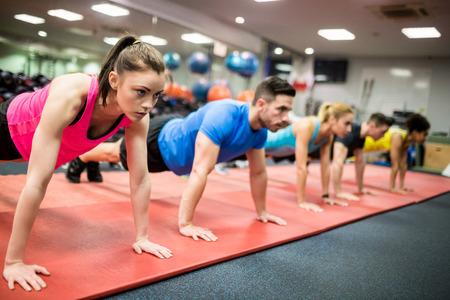 adentro y afuera: Las personas en forma de trabajo en clase de fitness en el gimnasio Foto de archivo