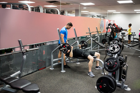 weight room: Fit people working out in weights room at the gym