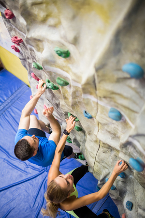 recreational climbing: Fit woman rock climbing indoors in the gym