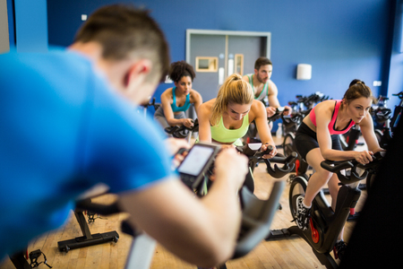 teacher in class: Fit people in a spin class at the gym
