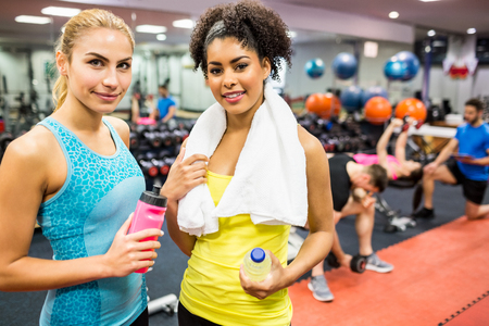 fit women: Fit women smiling at camera in weights room at the gym Stock Photo