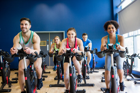 exercise bike: Fit people in a spin class the gym Stock Photo