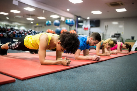 working out: Fit people working out in fitness class at the gym Stock Photo