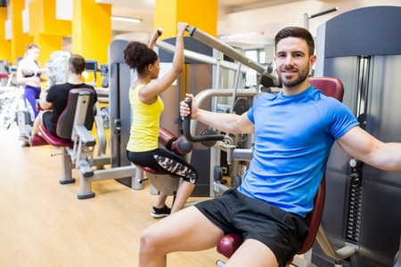 young adult men: Fit people using weights machines at the gym