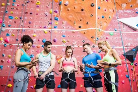 trepadoras: Las personas en forma que se preparan para escalar las rocas en el gimnasio