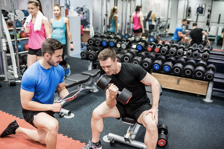 man working out: Fit man working out in weights room at the gym Stock Photo