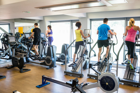 step well: Fit people working out using machines at the gym