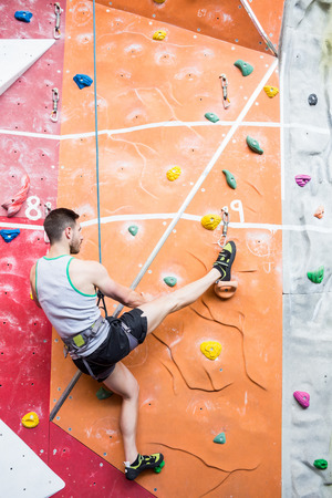 escalando: Hombre roca Fit escalada bajo techo en el gimnasio