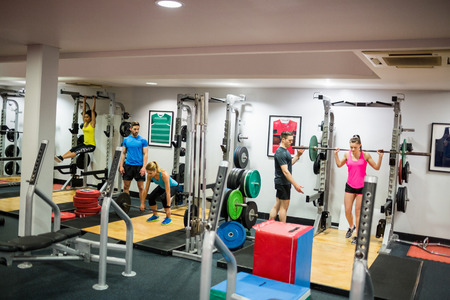 working out: Fit people working out in weights room at the gym