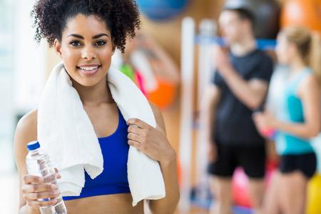 fitness hombres: Ajustar la mujer sonriendo a la cámara en el gimnasio