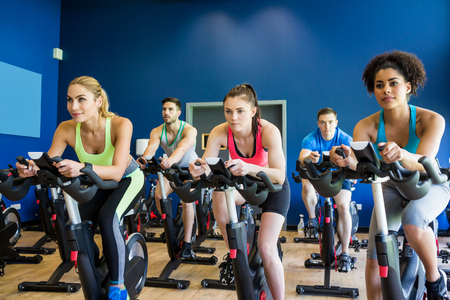 exercise equipment: Fit people in a spin class at the gym