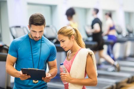 portapapeles: Entrenador y el cliente discutir su progreso en el gimnasio
