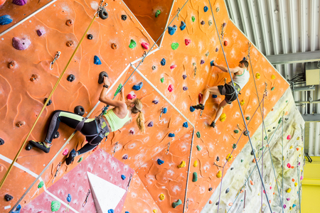 man climbing: Fit couple rock climbing indoors at the gym Stock Photo