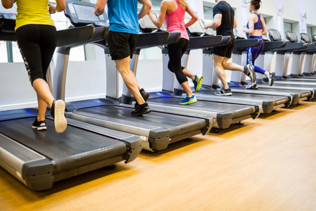 gym: Fit people jogging on treadmills at the gym Stock Photo