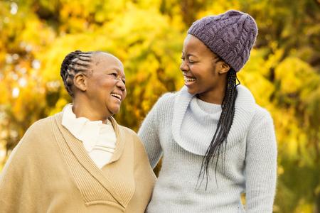 mujeres negras: Madre y abuela sonriendo el uno al otro en un parque