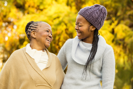 happy black woman: Mother and grandmother smiling to each other in parkland Stock Photo