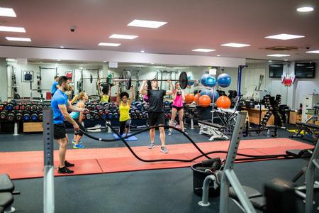 gimnasio: Las personas en forma de trabajo a cabo en la sala de pesas en el gimnasio