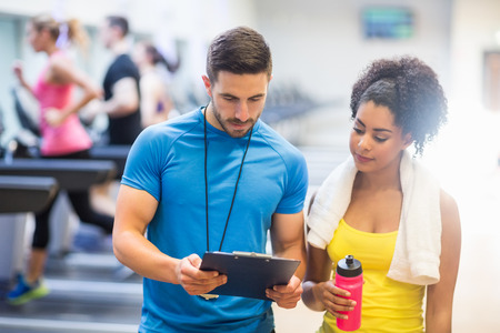 Fit woman talking to her trainer at the gym