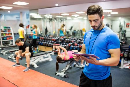 resistencia: Entrenador hermoso que usa la tableta en la sala de pesas en el gimnasio Foto de archivo
