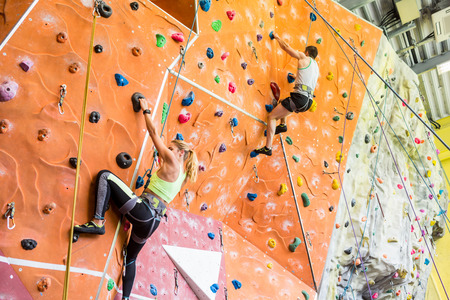recreational climbing: Fit couple rock climbing indoors at the gym Stock Photo