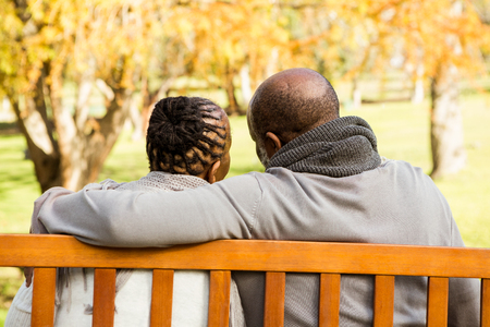 jubilados: Feliz pareja senior discutiendo juntos en un banco en un parque