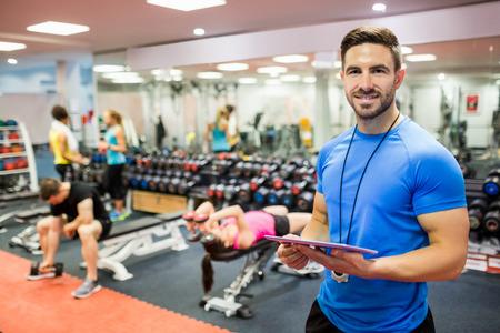 levantar pesas: Entrenador hermoso que usa la tableta en la sala de pesas en el gimnasio Foto de archivo