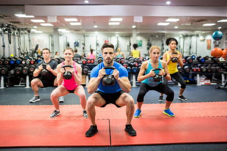 kettlebell: Fit people working out in fitness class at the gym Stock Photo