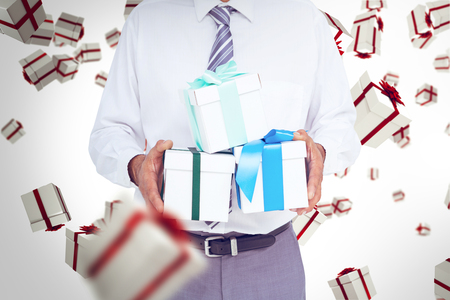 Businessman holding gifts against white and red gift box