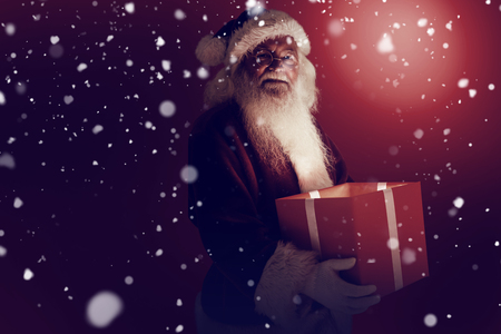 pere noel: Père Noël tenant un cadeau contre la neige