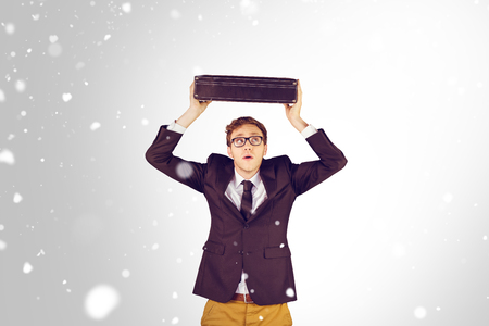 geeky: Young geeky businessman holding briefcase against snow