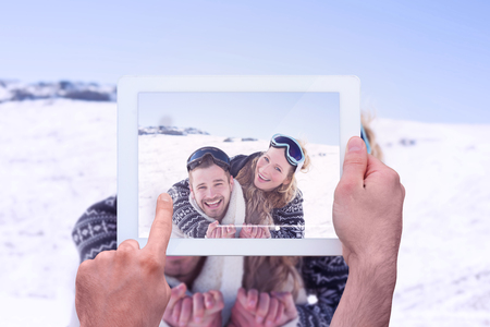 ski goggles: Hand holding tablet pc against cheerful couple with ski goggles on snow