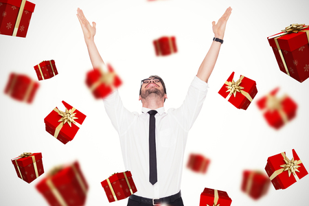 businessman present: Smiling businessman cheering with his hands up against red and gold presents