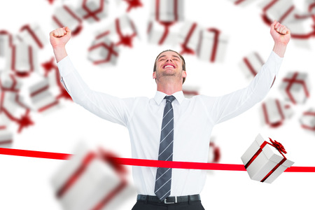 finish line: Happy businessman crossing the finish line against white and red gift box
