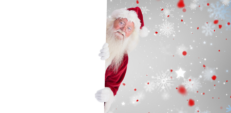 peep out: Santa looks out behind a wall against snowflake pattern Stock Photo