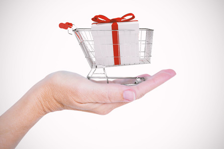gift spending: Close up view of hand  against trolley full of gifts