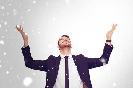 Businessman cheering with hands raised against snow
