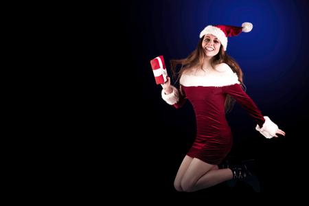 pere noel sexy: Rousse Festive sauter avec un cadeau sur fond blanc