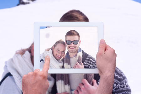 snowed: Hand holding tablet pc against smiling couple in front of snowed hill Stock Photo