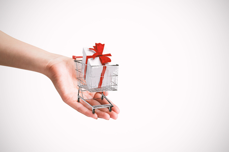 gift spending: Hand presenting against trolley full of gifts Stock Photo