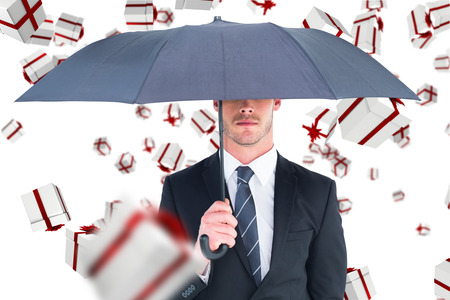 unsmiling: Unsmiling businessman sheltering under umbrella against white and red gift box Stock Photo