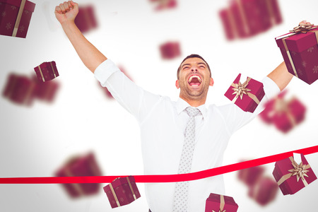 finish line: Businessman crossing the finish line against red presents Stock Photo