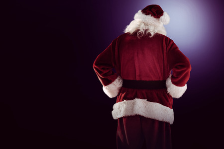 father: Rear view of father christmas on dark background Stock Photo